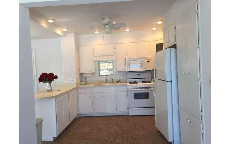 a kitchen with a tiled floor and white cabinets, a white fridge, and a white oven