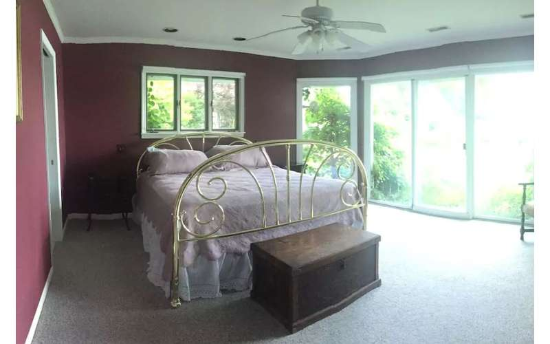 a large bed with a chest in front of it near a sliding glass foor