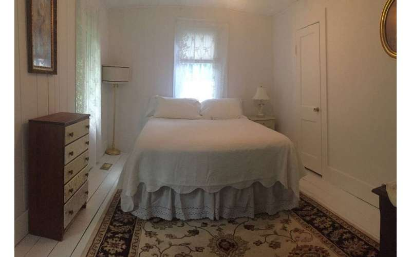 a bedroom with a white bed near a wooden dresser