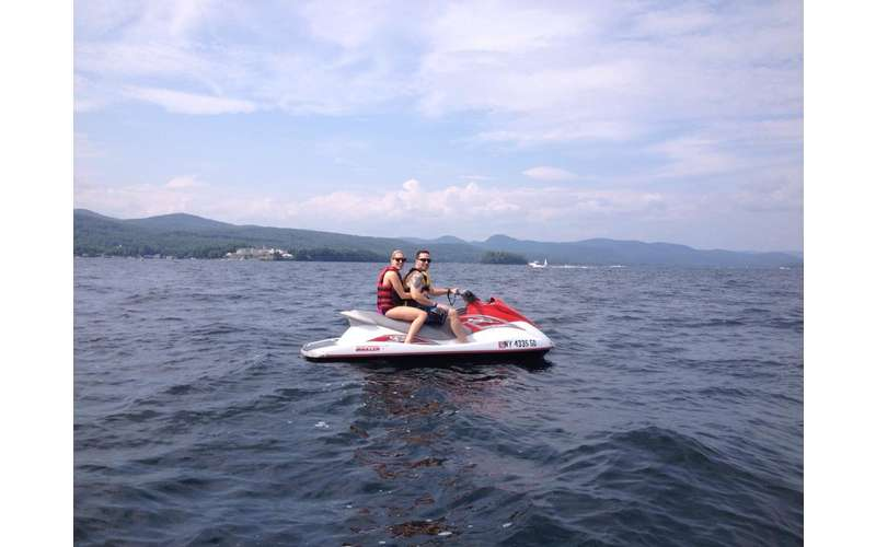 a man and a woman riding on a jet ski in the middle of a lake