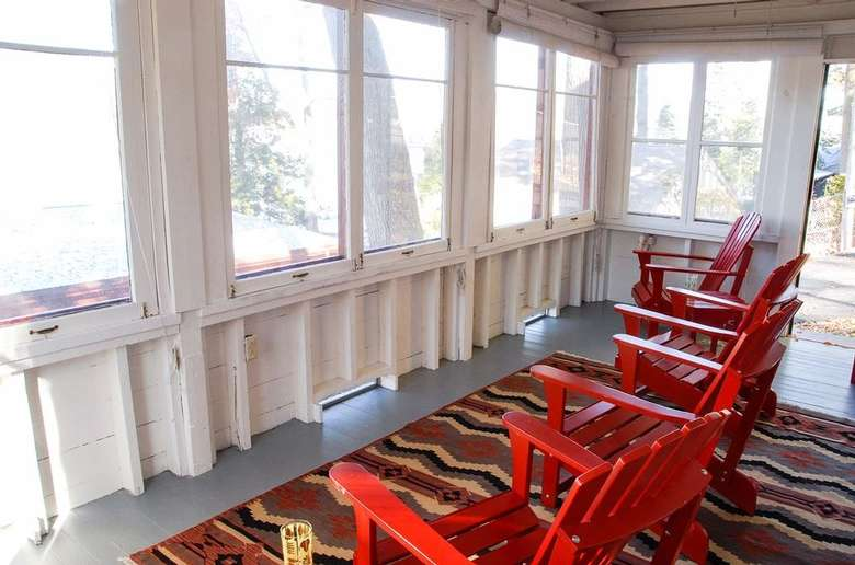 red adirondack chairs in an enclosed porch