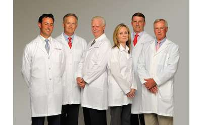 a group of six plastic surgeons standing together with their white lab coats on