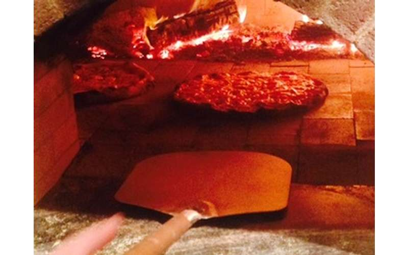pizza rests inside a wood oven, ready to be taken out