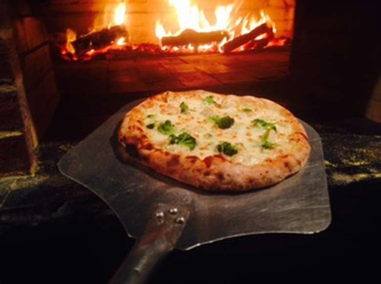 a white pizza with broccoli about to be put in a wood fired oven