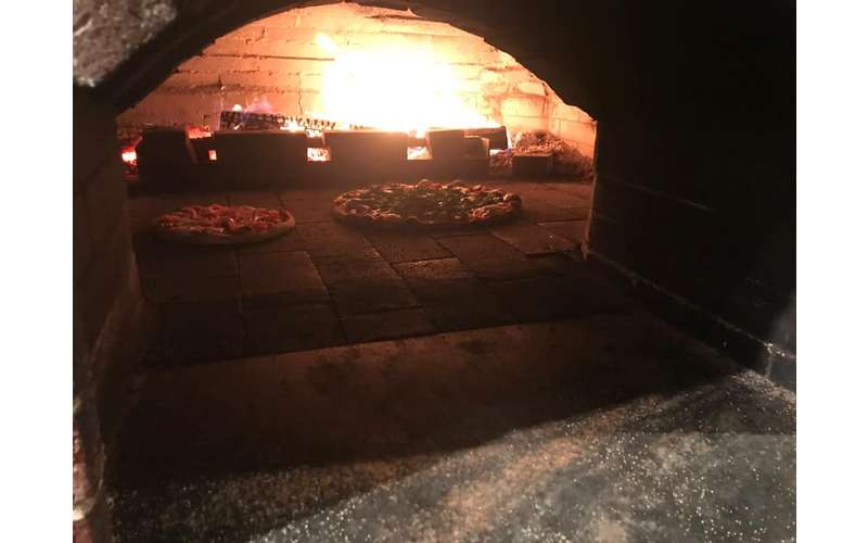 two pizzas inside an oven