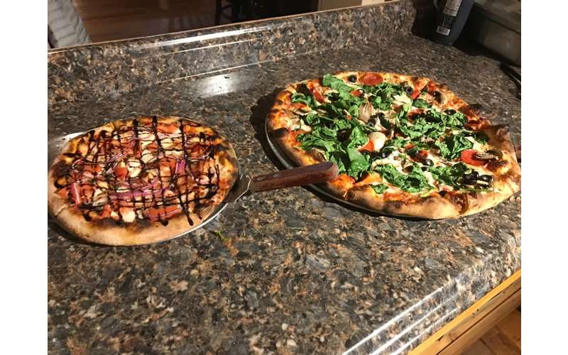 two specialty pizzas on a table