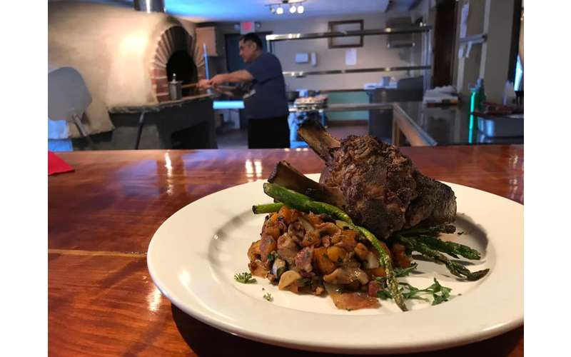 what looks like lamb chops with asparagus and potatoes on a plate