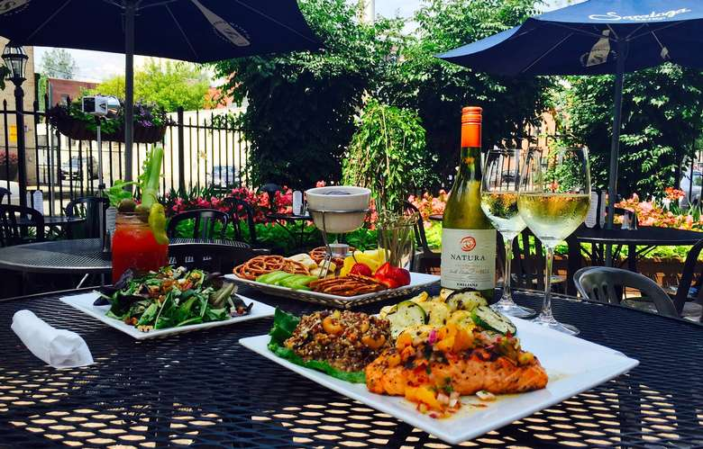 restaurant table on a patio with three plates of food, two glasses of white wine, and a bloody mary on it