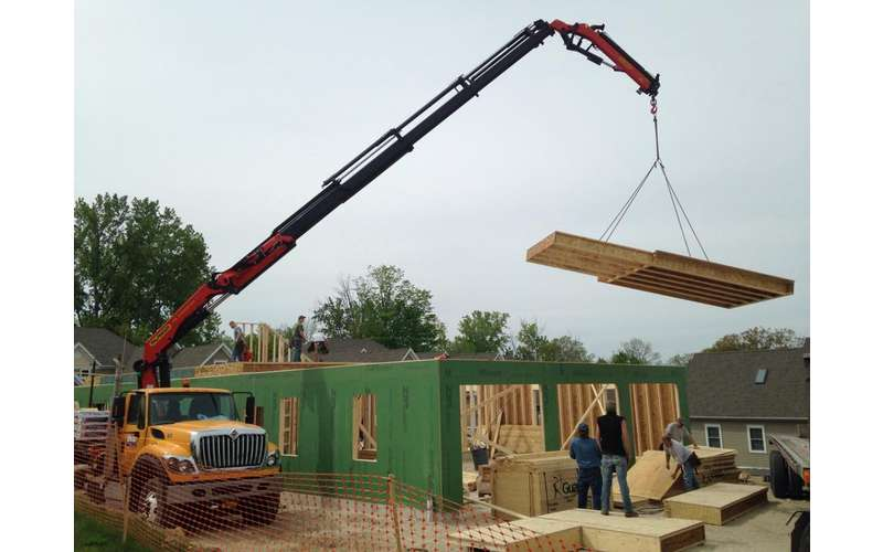 a large crane holding sections of wood for a house building project