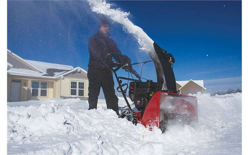 a man pushing a snow thrower