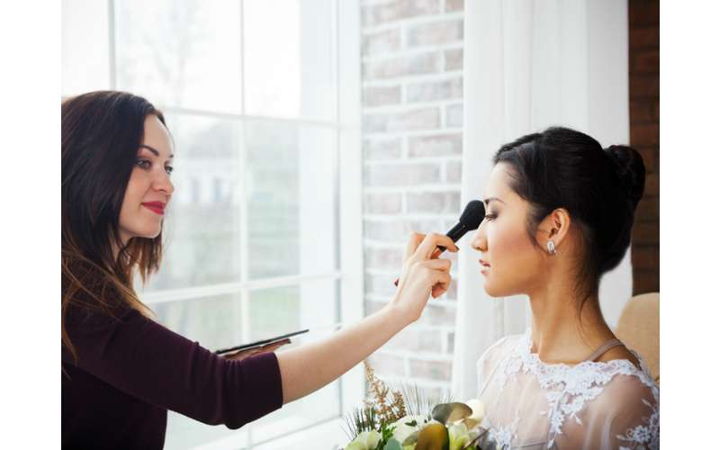 a woman brushing makeup on another woman's face