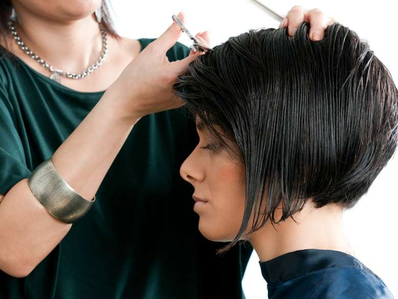 a woman giving another woman a hair cut