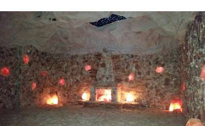 a brightly lit pink salt cave with multiple lights on the walls