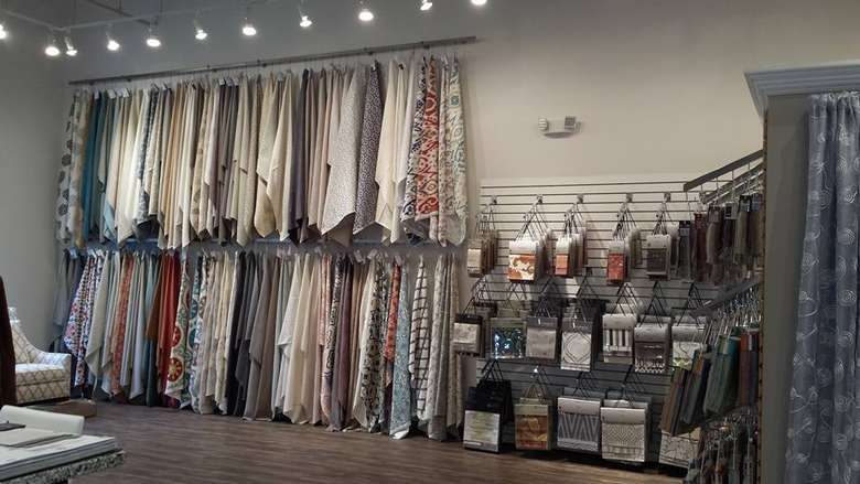 different fabrics hanging on a wall near other samples on racks