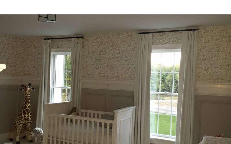 a baby's room with a crib and windows with curtains