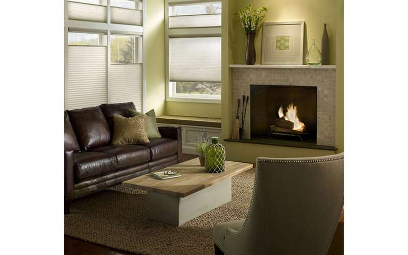 a living room with a brown leather couch, a chair, a table, and a fireplace
