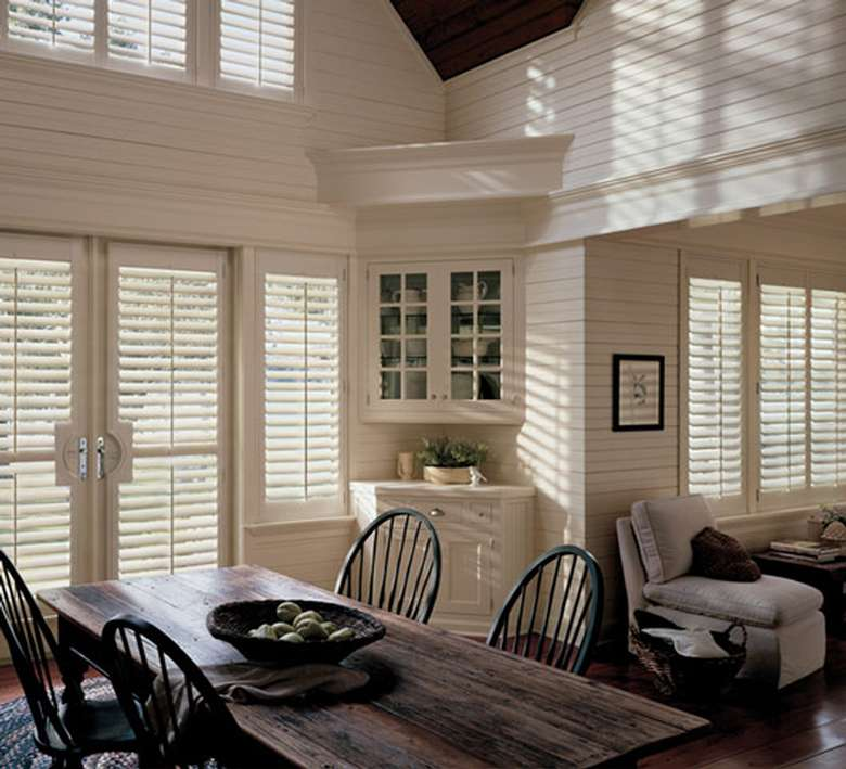 a spacious dining room in a house with doors with shutters and white walls