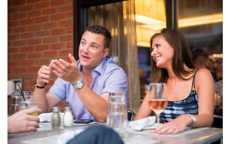 a man sitting next to a woman at an outdoor patio table