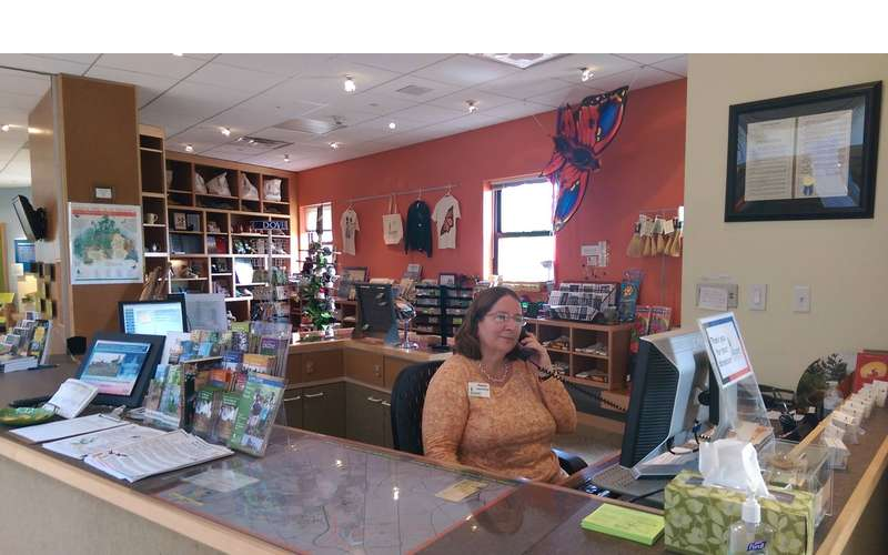a woman sitting at a desk near a gift shop