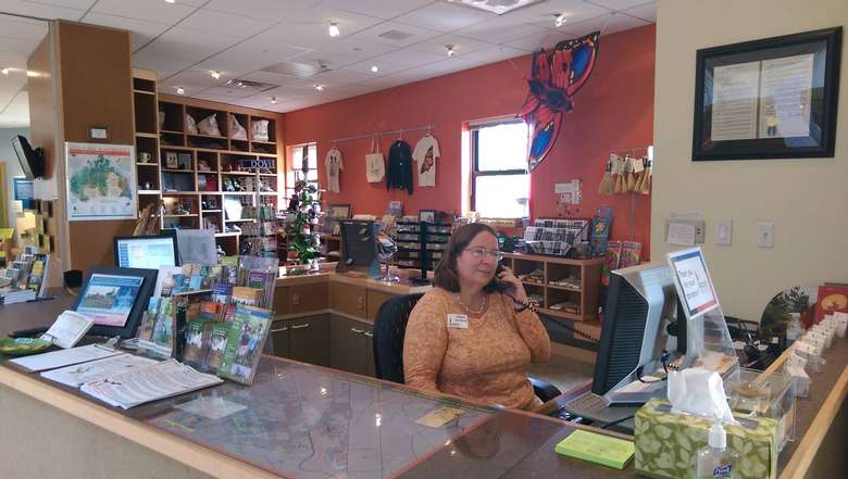 a woman sitting at a desk near a gift shop