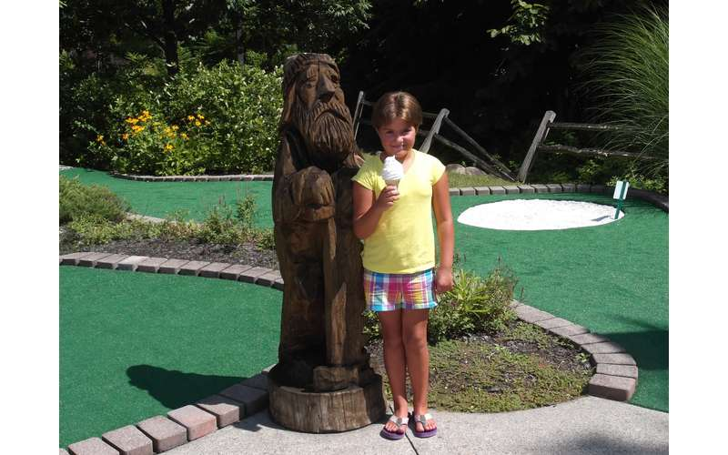 a girl standing in front of a wooden statue on a mini golf course while holding an ice cream cone