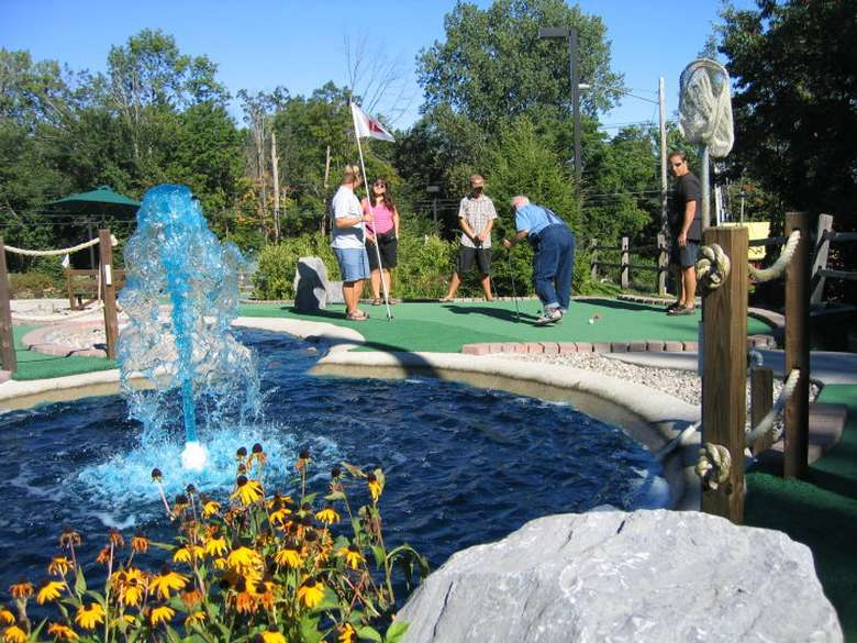 a mini golf course with a large blue fountain