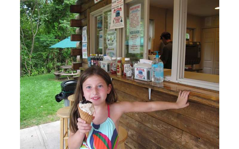 a little girl poses in front of the snack stand with an ice cream cone