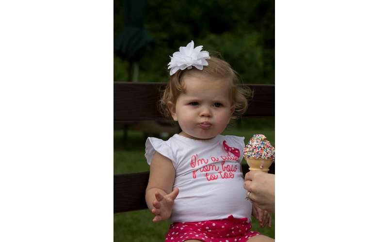 a toddler girl with a vanilla ice cream cone with sprinkles being handed to her, her shirt says I'm cute from bow to toe