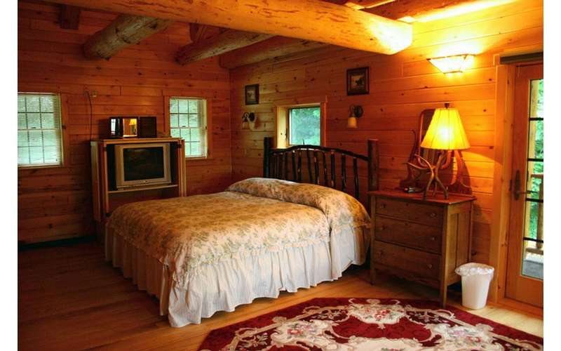 a spacious rustic bedroom with a tv near the bed