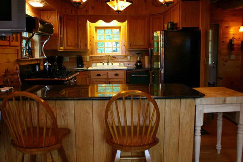 a counter with chairs near a kitchen with a fridge, sink, oven, and more