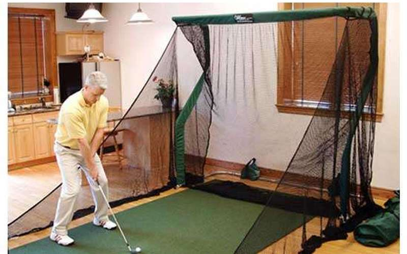 Man practicing golf indoors using a net