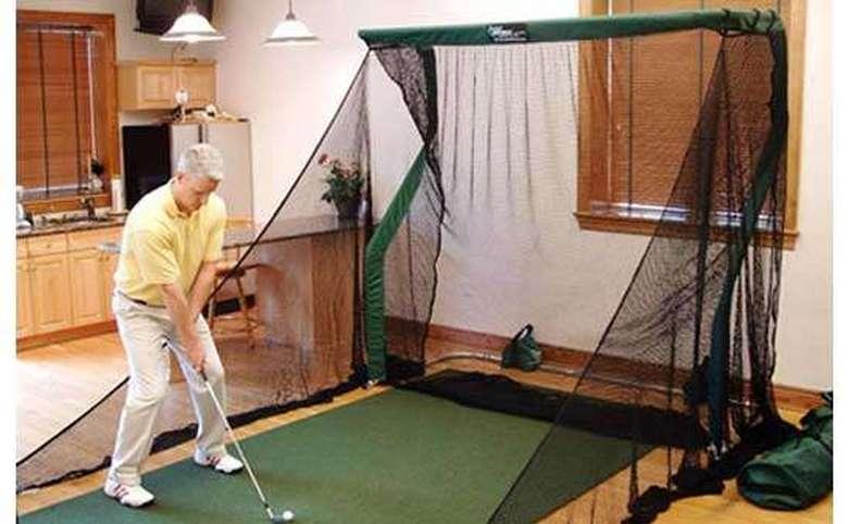 Man practicing golf indoors using a net