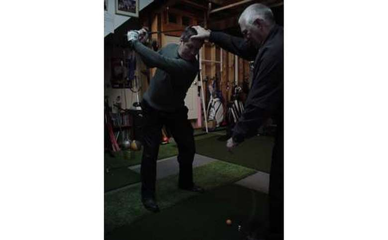 Man instructing another man on how to improve his golf swing