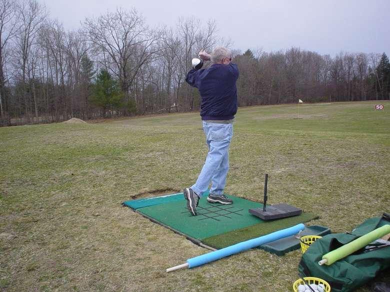 Man golfing off a tee