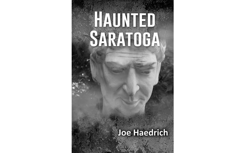 a book called Haunted Saratoga by Joe Haedrich with a creepy face