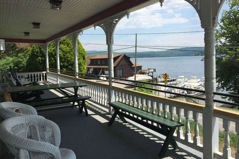 view of the lake from a spacious porch with chairs and benches