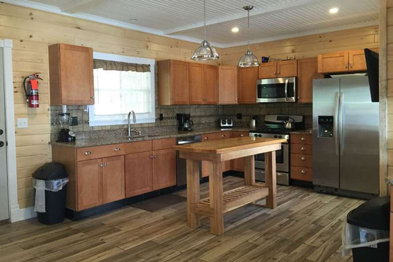 a spacious kitchen with a lot of cabinet space, stainless steel fridge, small wooden table