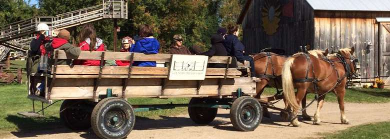 a large wagon with riders sitting in the back