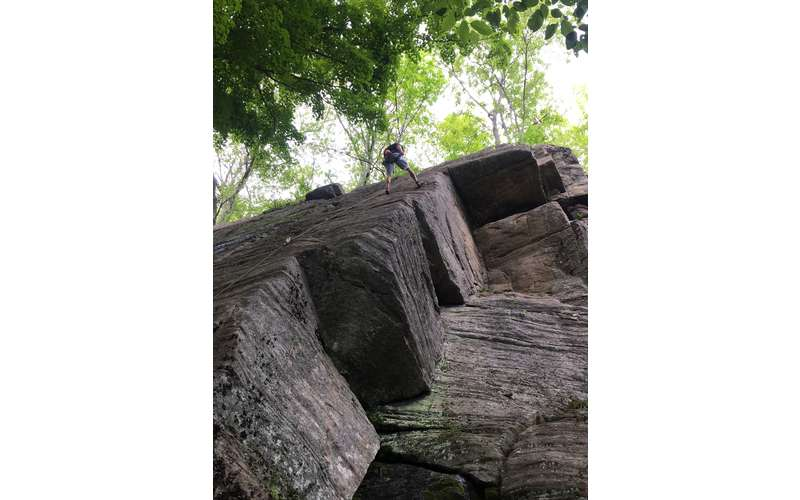 a man rock climbing up a steep rock
