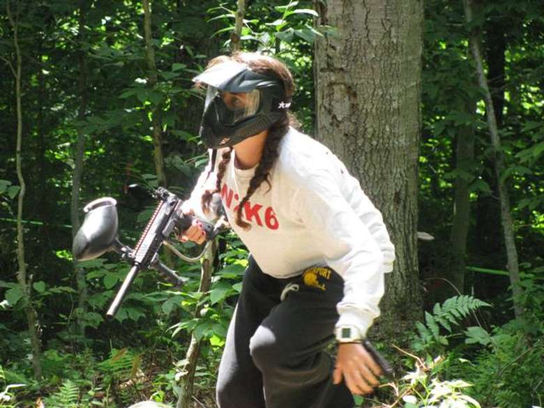 a woman in the woods with paintball gear on