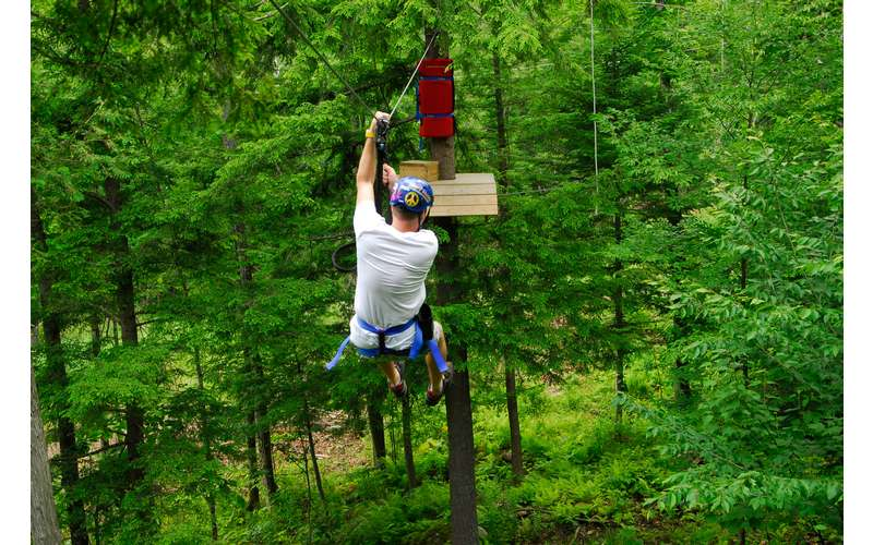 a man on a zipline in the trees