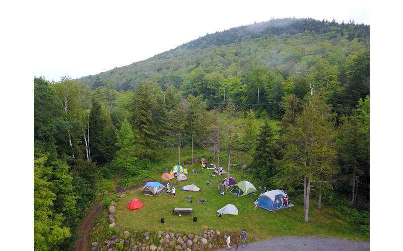 an aerial view of a campsite with multiple tents and campers