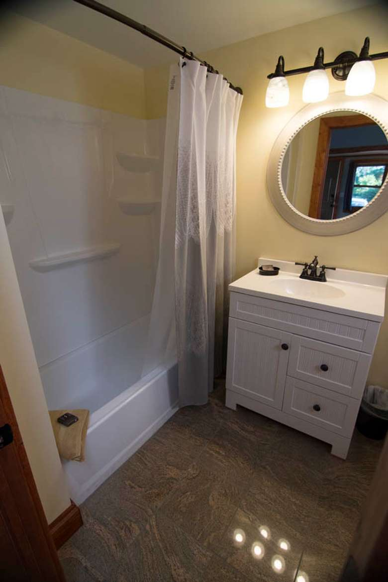 a bathroom with a shower, mirror, and sink