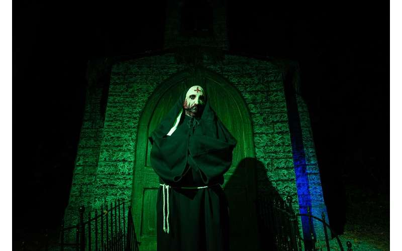 man dressed in scary cult outfit at a horror attraction