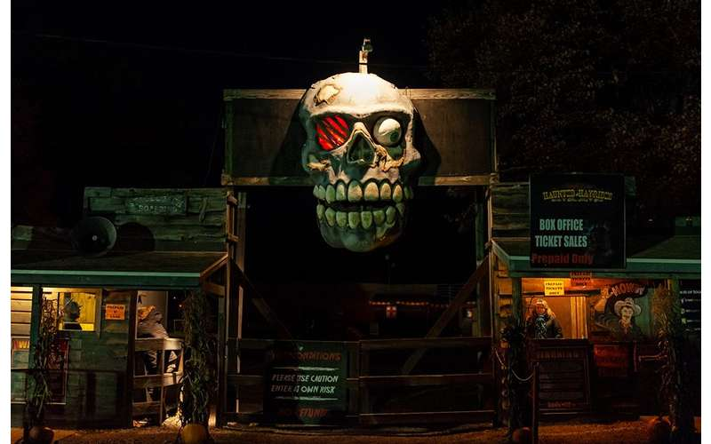skull decor at the entrance of a haunted hayride gate