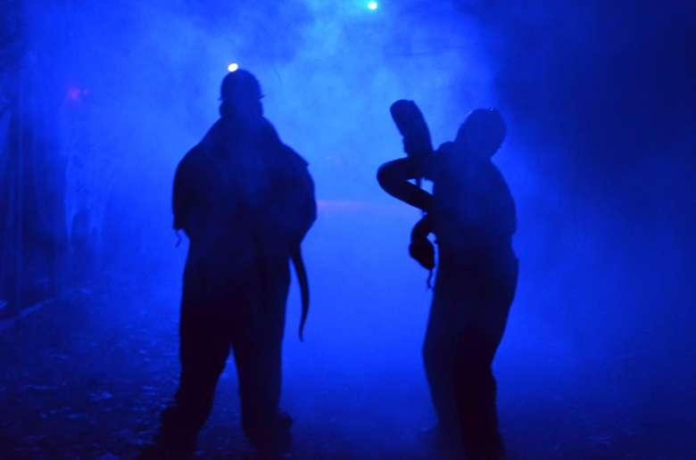 two people at horror attraction in a blue smokey light