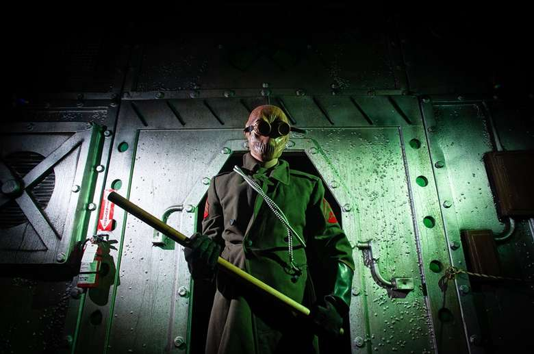 man dressed in trenchcoat at a horror attraction