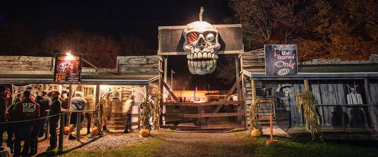 skull on top of a gate entrance of a haunted hayride
