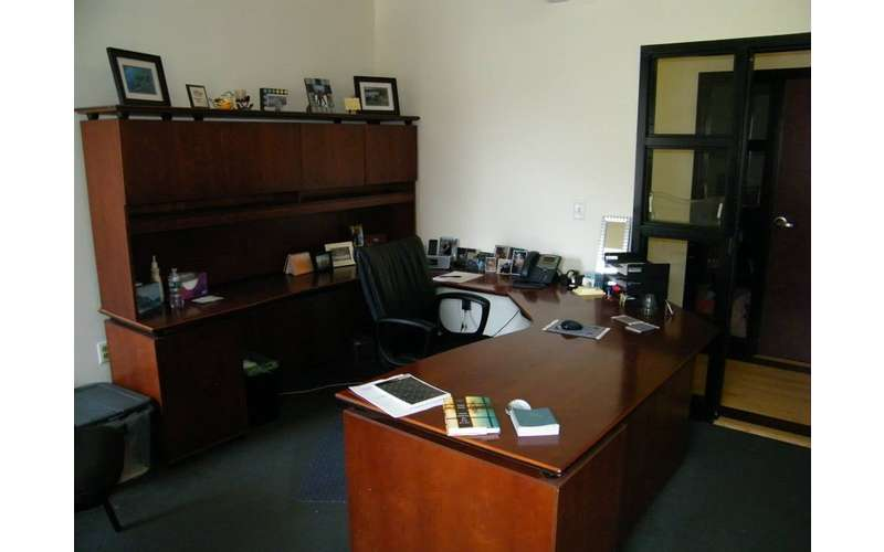a dark brown computer desk in an office with a phone, photos, and other decor