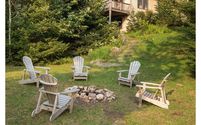 Adirondack chairs around a fire pit
